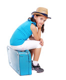 Little girl sitting on the blue suitcase