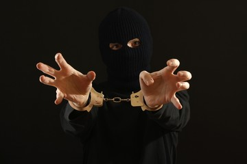 Angry bandit in black mask handcuffed isolated on black