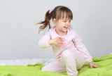Little girl sitting on bed on wall background