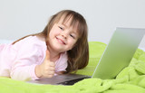 Little girl with laptop on bed on wall background