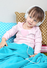 Little girl sitting on pillows on wall background