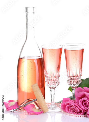 Composition with pink sparkle wine in glasses, bottle and pink