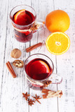 Mulled wine with oranges and spices on wooden background