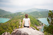 Woman sitting on top of a mountain and enjoying view
