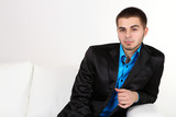 Handsome young man sitting on sofa on light background