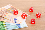 Red dices and money, on wooden background