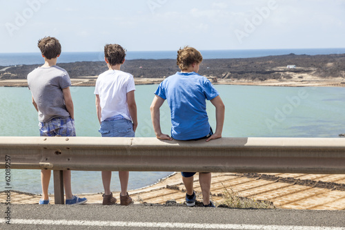 three boys leaning at guide rail