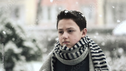 Young sad boy in snowy weather