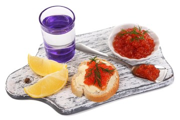 Sandwich with caviar and vodka on wooden board isolated on