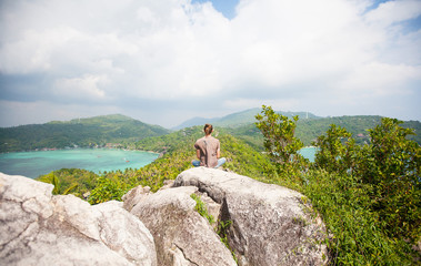 Man sitting on top of a mountain and enjoying view