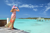 Girl on the wooden jetty looking to the ocean. Exuma, Bahamas