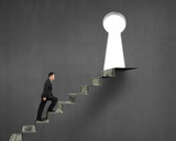 man climbing on money stairs to key hole