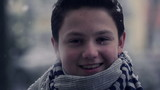 Happy young boy in snowy weather, super slow motion