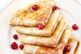 Pancakes with cranberry berries and honey on a plate