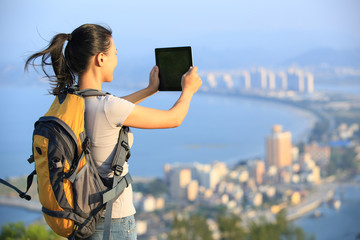 woman hiker use digital tablet on seaside mountain peak