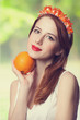 Beautiful redhead women with wreath and orange