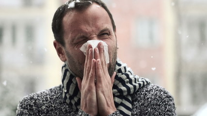 Sick man blowing his nose in snowy weather