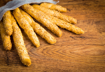 Sesame breadsticks on wooden background