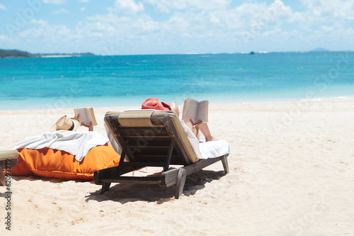 couple of people reading while sunbathing on the beach