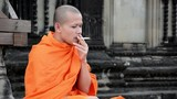 cambodian monk smoking in angkor wat temple