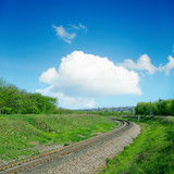 railroad in green landscape and clouds over it