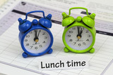 Lunch time card with miniature clocks showing 12 and 1 o'clock