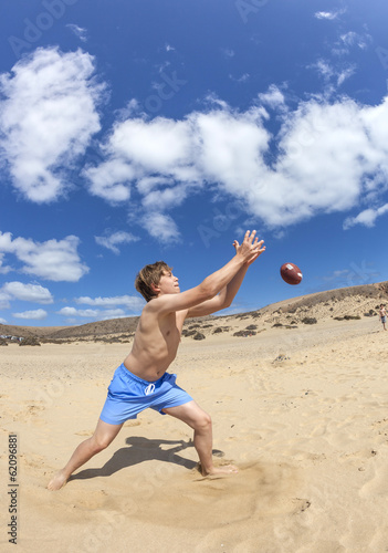 boy enjoys playing ball at the beach