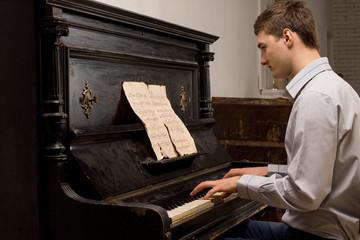 Young man practising at a piano