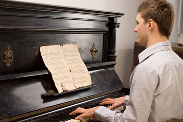 Young man playing music on a wooden piano