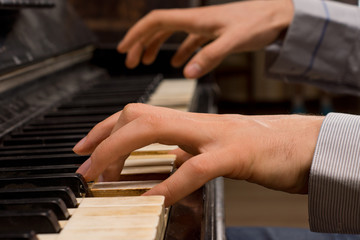 Male pianist playing music on an ivory keyboard