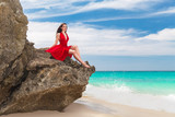 young beautiful alone woman in red dress sitting on the rock on