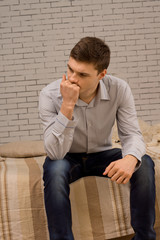 Worried young man sitting deep in thought