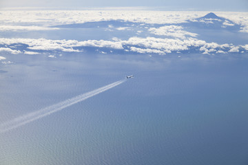 Airplane airline overflying ocean and volcanic island