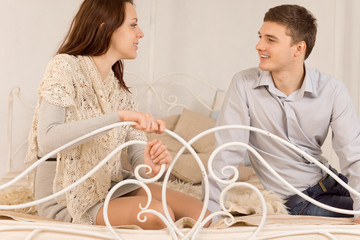 Young happy couple sitting chatting on a bed