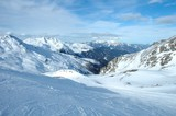 Ski slope, peaks and valley in Alps in winter