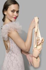 Ballerina holding tutu, beautiful woman raising ballet shoes