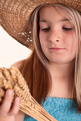 girl with the freckles and straw hat holding in his hand a  whea