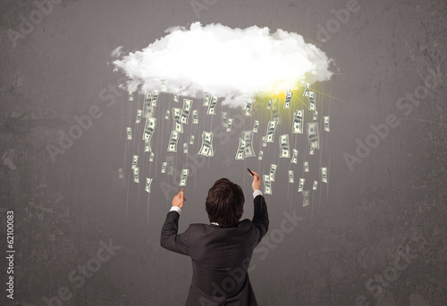 Business man in suit looking at cloud with falling money