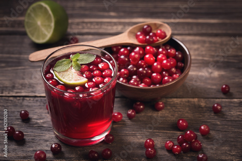 Leinwanddruck Bild Cranberry juice on old wooden table