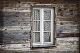 Rural much neglected window in wooden wall of house