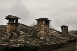 Old stone tiles slide-roof house with stone chimneys