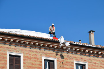 The man shoveling snow on roofs