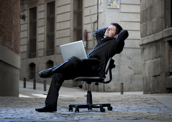 Happy Business Man sitting on Office Chair on Street with laptop