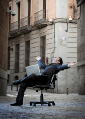 Business Man sitting on Office Chair on Street with Computer
