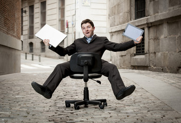 business man rolling downhill on chair with computer and tablet