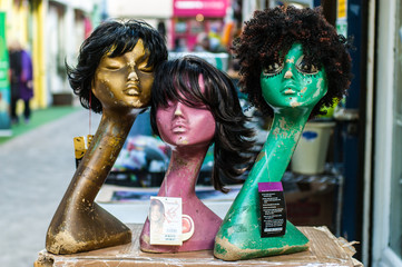 Three coloured mannequins wearing wigs in an outdoor market