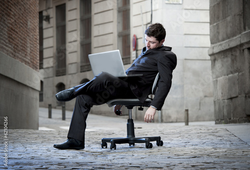Tired Business Man sitting on Office Chair on Street sleeping - 62104266