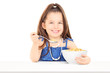 Cute little girl eating cereal from a bowl