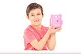 Little boy holding a piggybank