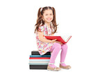Little girl posing seated on a stack of books